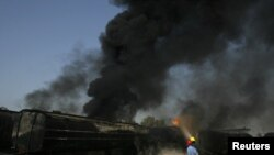 Pakistani firemen extinguish a fire on a burning oil tanker on a highway near Shikarpur, Pakistan, on October 1.