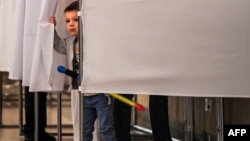 A young boy peeps out from behind the curtains of a voting booth at a polling station during the municipal elections in Moscow on September 10.