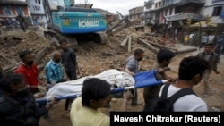 Rescue workers remove the body of a victim in Kathmandu.