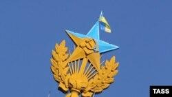 Звезда, раскрашенная в цвета флага и флаг Украины на шпиле высотного жилого дома на Котельнической набережной в Москве.