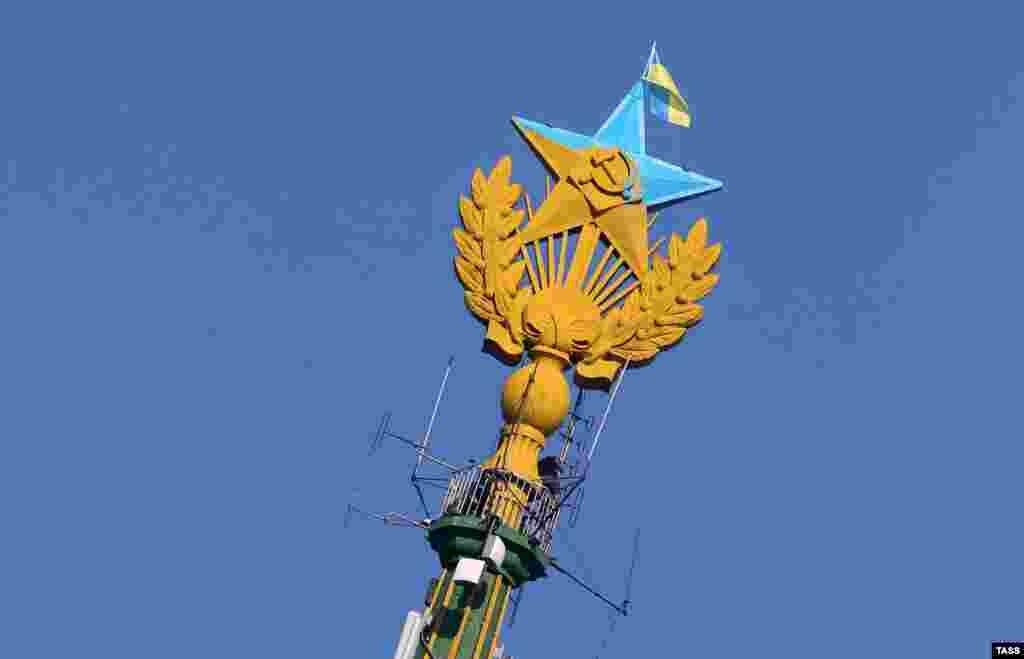 Радянська зірка перемальована в українські кольори та український прапор на будівлі сталінської висотки розташованої на Котельницькій набережній, Москва, 20 серпня 2014 року