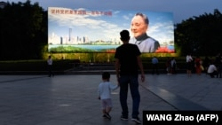 Мужчина с ребенком на фоне гигантского портрета бывшего лидера Китая Дэн Сяопина. Шэньчжэнь, 8 ноября 2018 года.