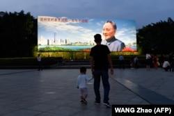 Отец и сын смотрят на плакат с изображением Дэн Сяопина в городе Шэньчжэнь, провинция Гуандун