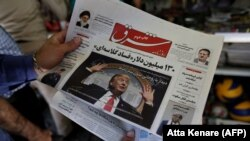 "A man takes a glance at a newspaper with a picture of U.S. president Donald Trump on the front page, in the capital Tehran. The headline on photo says ""Meeting with Rouhani without preconditions."" July 31, 2018"