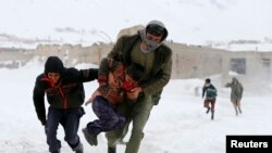FILE: Survivors of an avalanche run to get relief goods distributed by an Afghan army helicopter in the Paryan district of Panjshir province.