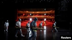 Volunteers from the Blue Sky Rescue team disinfect at the Qintai Grand Theatre in Wuhan, April 2, 2020
