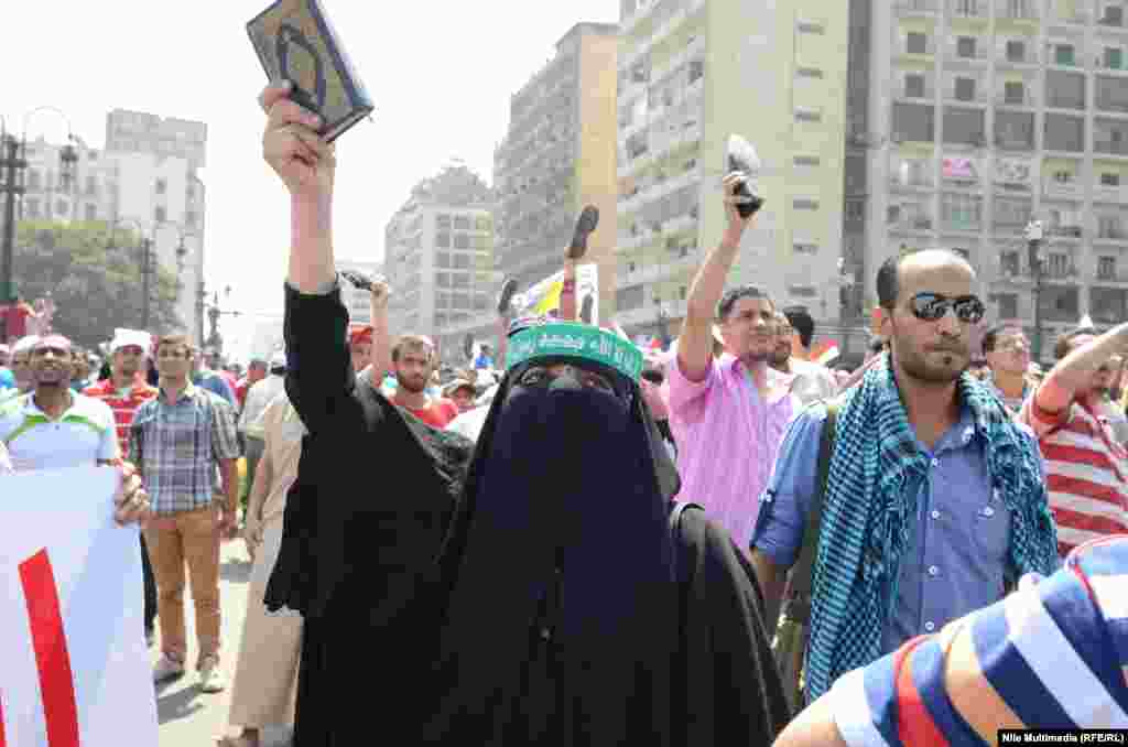 A woman holds the Koran aloft as supporters of ousted Egyptian President Muhammad Morsi take to the streets in Cairo on August 16. (RFE/RL/Ahmed Ragab)