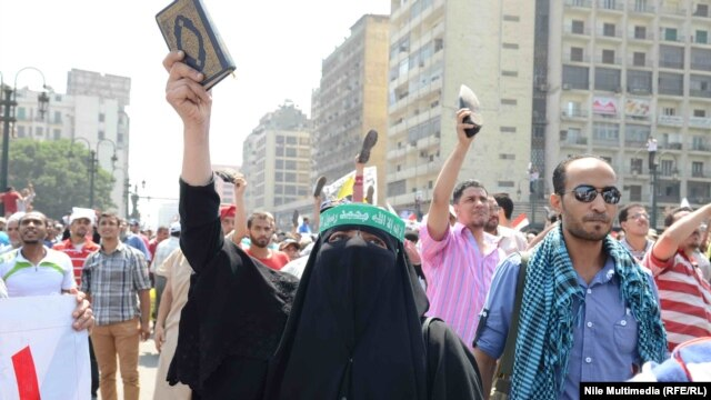 A woman holds the Koran aloft as supporters of ousted Egyptian President Muhammad Morsi take to the streets in Cairo on August 16.