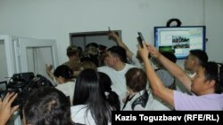 """Представители СМИ бросились снимать попытку вывести Искандера Еримбетова силой из зала судебного заседания. Его сторонники начали скандировать """"Искандер! Искандер!"""" Алматы, 14 июня 2018 года."""