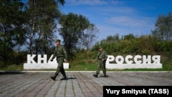 "Russian guards walk past signs that read ""DPRK"" (Democratic People's Republic of Korea) and ""Russia"" at the border crossing between Russia and North Korea."
