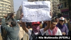 """A young protester during the antigovernment demonstrations in Cairo's Tahrir Square in February 2011: """"Enough already, my arms hurt!"""""""