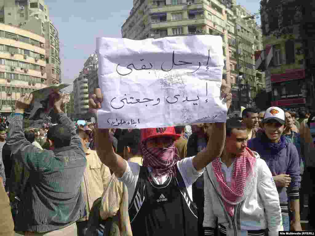 "A young protester holds a banner reading ""Go away then, my arm is hurting."""