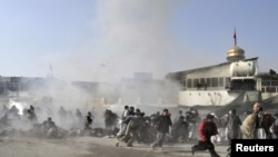 People react seconds after the suicide blast ripped through a Shi'ite gathering in Kabul on December 6.