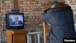 Ресей телеарнасының хабарын қарап отырған адам. (Көрнекі сурет)
