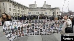 Preživjeli Bošnjaci nose baner sa fotografijama žrtava rata u BiH, ispred Tribunala u Hagu na dan izricanja presude Radovanu Karadžiću, mart 2016.
