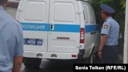 Сотрудники полиции рядом с полицейским микроавтобусом.
