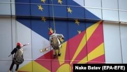 Radnici peru prozore na kojima su zastave Evropske unije i Severne Makedonije u Skoplju, februar 2019. godine