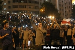 Protesters hold cellphone flashlights aloft at a protest rally on August 9-10.