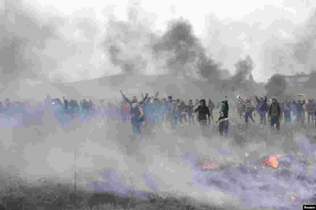 Біженці, які хочуть перейти кордон з Північною Макаденією, стоять серед диму під час сутичок за межами табору «Діавата» на півночі Греції
