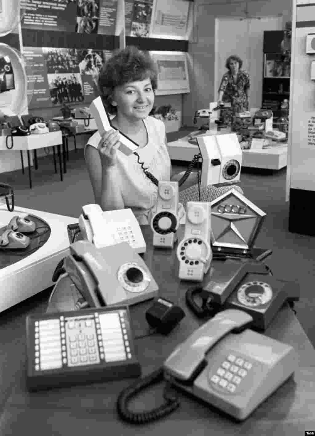 A woman displays products and a State Quality Mark of the U.S.S.R., the highest certification of quality, in the shop at the Perm telephone production plant in 1982.