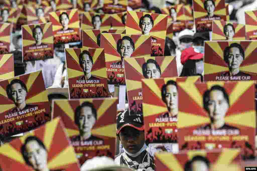 Прихильники Аун Сан Су Чжи римо-католицького віросповідання тримають плакати із зображенням затриманої цивільної лідерки М'янми під час протесту проти військового перевороту на акції біля будівлі посольства Китаю в Янгоні, М'янма, 21 лютого 2021 року