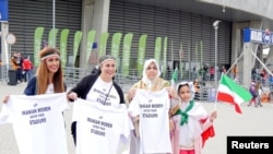Women hold t-shirts as they protest for Iranian women's rights to enter stadiums in Iran, ahead of the FIVB Volleyball World League