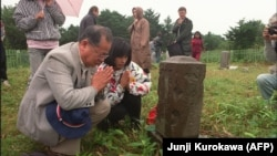 In a 1989 photo, Japanese visitors pray at a cemetery in Kunashir, part of the disputed island chain.