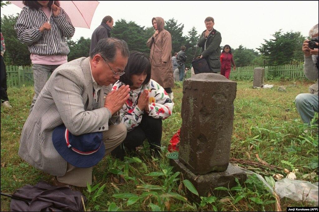"""Ish banorët japonez duke i vizituar varrezat e të afërmve në ishullin Kunashir. Analistët sygjerojnë se """"alfa"""" mund të përfshijë të drejtat për peshkim për Japoninë afër dy ishujve më të mëdhenjë ose të drejtat e qytetarëve japonez për të vizituar dhe për të krijuar biznese në ishujt e kontestuar. Nëse Rusia dhe Japonia mund ta gjejnë një """"alfa"""" që është e përshtatshme për të dyja anët, një traktat i paqes mund të nënshkruhet dhe lufta e dytë botërore mund të përfundoj."""