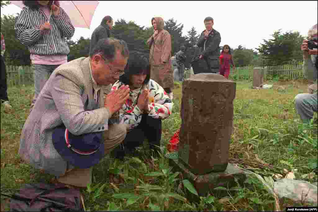"""Japanese former residents visiting relatives' graves on Kunashir Island. Analysts suggest that """"alpha"""" might include fishing rights for Japan near the two larger islands or the rights for Japanese citizens to visit and do business on the disputed islands. If Russia and Japan can find an """"alpha"""" that is acceptable to both sides, a peace treaty can be signed and World War II might finally, formally end."""