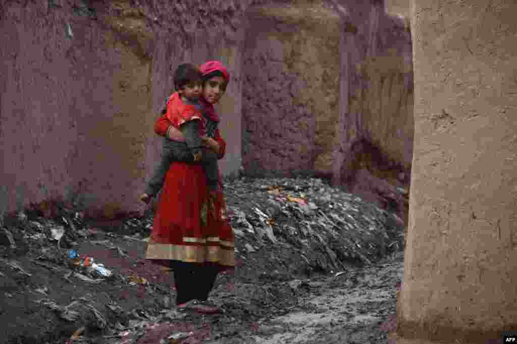 An Afghan girl holds her brother as she walks through a camp for the internally displaced in Herat. (AFP/Aref Karimi)