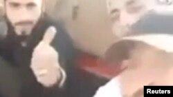 تصویر، گروهی از افراد حاضر در جریان بریده شدن سر کودک را نشان میدهد. فرد سیاهپوش صورت کودک ۱۲ ساله را در درست گرفته و به دوربین نشان میدهد. آنها از خودشان فیلم گرفتهاند.