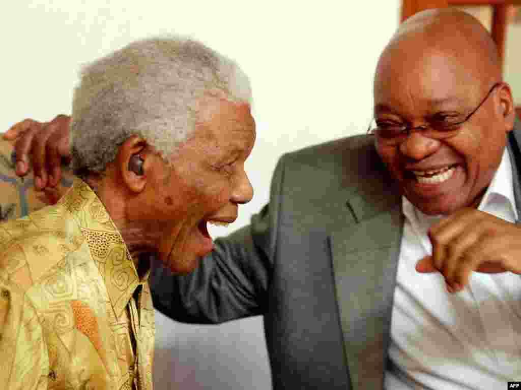 Былы прэзыдэнт ПАР і ляўрэат Нобэлеўскай прэміі міру Нэльсан Мандэла і прэзыдэнт ПАР Якаб Зума разам сьмяюцца падчас абеду для былых палітвязьняў апартэіду. Афіцыйная рэзыдэнцыя прэзыдэнта, Кейптаун, ПАР. Люты 2010