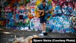 Собака слушает уличного музыканта у стены Леннона в Праге