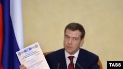 Рождение патриотов Россия стимулирует разными способами. Будущий президент страны держит в руках сертификат «материнского капитала» (январь 2007 года)