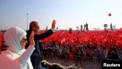 Прэзыдэнт Турэччыны Рэджэп Таіп Эрдаган з жонкай вітаюць людзей на мітынгу, арганізаваным на знак пратэсту супраць спробы вайсковага перавароту. Стамбул, 7 жніўня 2016 году