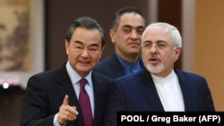Iran's Foreign Minister Mohammad Javad Zarif (right) arrives with his Chinese counterpart, Wang Yi, for a joint press conference in Beijing on December 5, 2016.