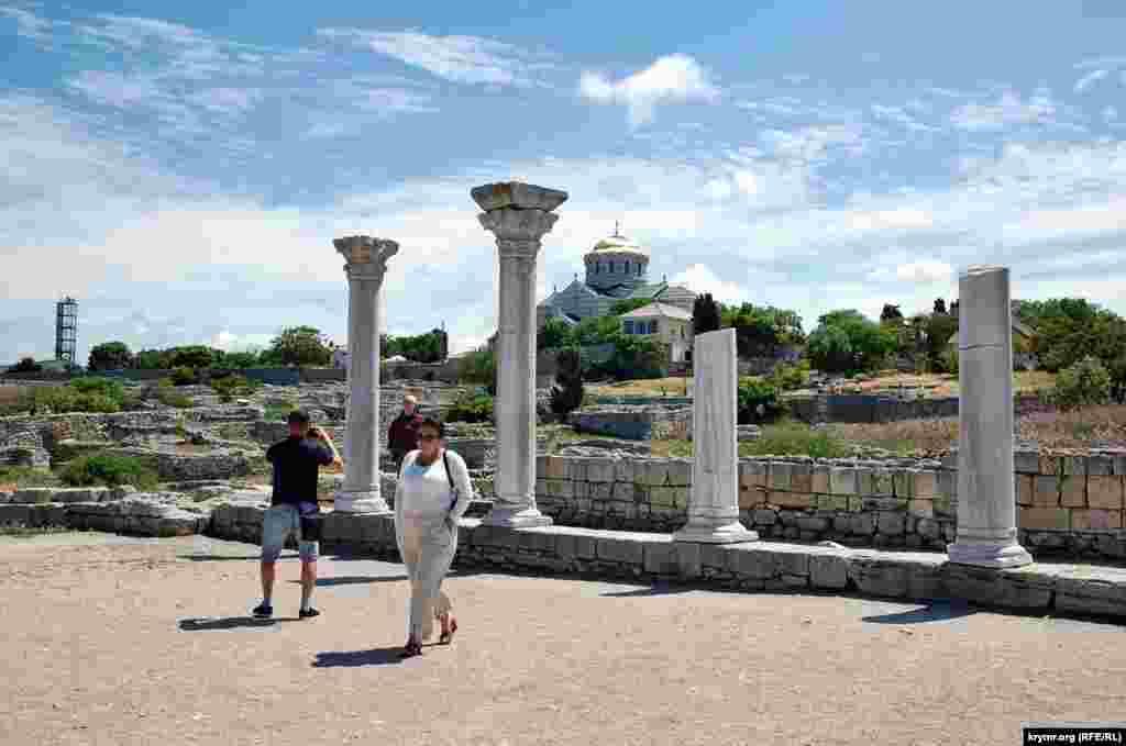 Туристы у колонн разрушенного античного древнегреческого храма, который находится на дальнем городище заповедника «Херсонес Таврический»