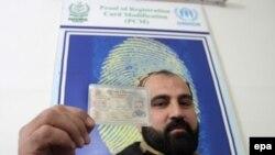 د پښتونخوا په هري پور کې یوه افغان کډوال خپله پېژند پاڼه ښيي.