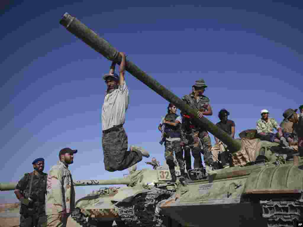 A transitional council fighter hangs from the gun turret of a tank in Wadi Dinar, Libya on September 21. (Photo taken by Alexandre Meneghini for AP)