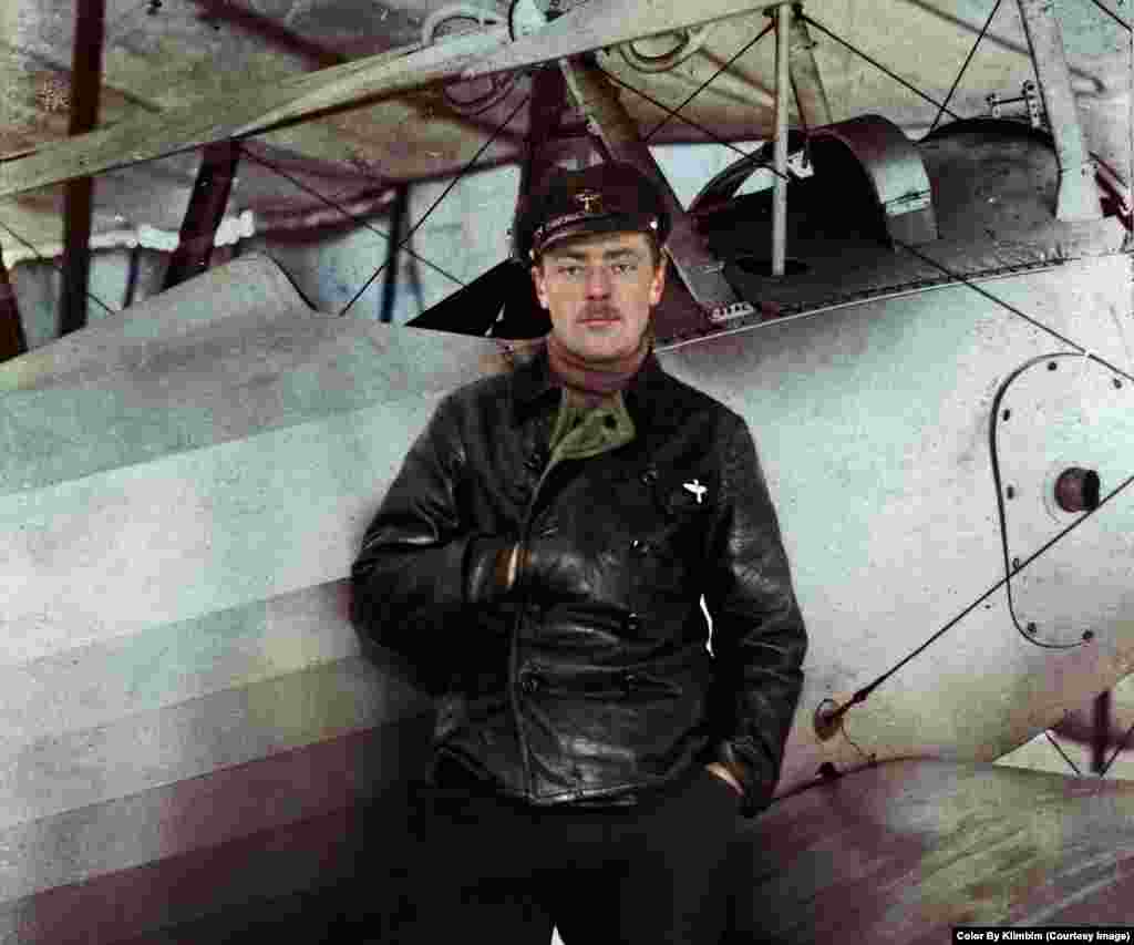 An unknown Russian pilot next to his biplane during World War I.