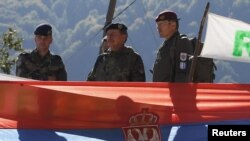 Kosovo Force (KFOR) Major General Erhard Drews of Germany stands along the barricades in front of a Serbian flag at the closed Serbia-Kosovo border crossing of Brnjak, on October 19.
