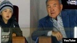 Қазақстан президенті Нұрсұлтан Назарбаев белгісіз бір ұл баламен хоккей тамашалап отыр. YouTube вебсайтынан алынған сурет.