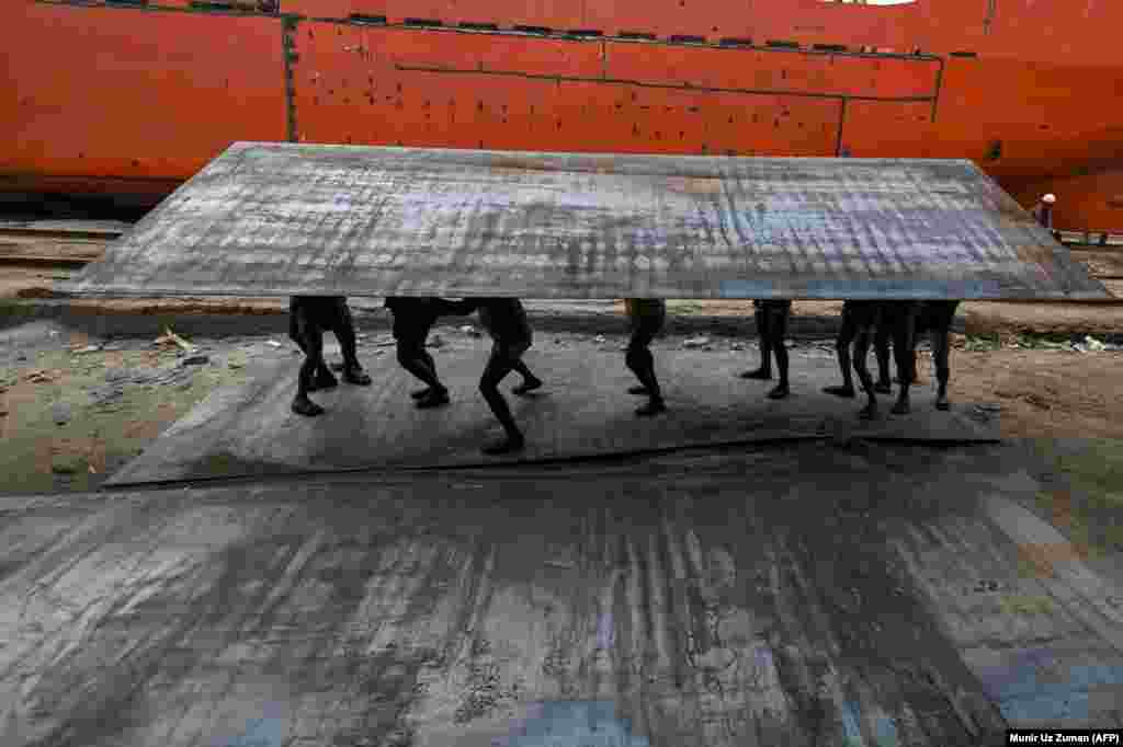 Bangladeshi laborers carry a heavy steel plate in a dockyard beside the Buriganga River in Dhaka. (AFP/Munir Uz Zaman)
