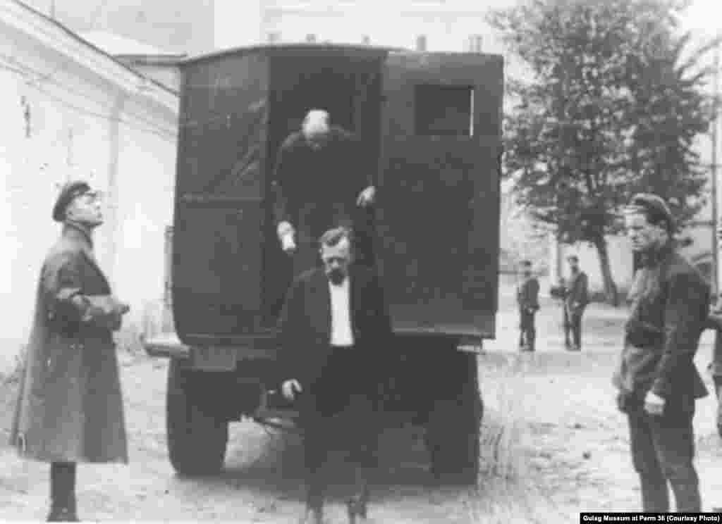Заключенные выходят из грузовой машины, переоборудованной в автозак.