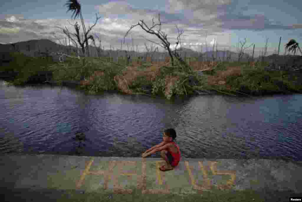 A boy sits on a message asking for help written in an area damaged by Typhoon Haiyan in Palo, Phillipines. (Reuters/John Javellana)