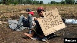 """Migrant koji štrajkuje glađu sa transparentom na kome piše """"Otvorite granice, molim vas"""", Horgoš 25. jul 2016."""