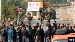 Люди стоять поряд з барикадами на прикордонному пункті Брняк, Косово, 16 вересня 2011 року