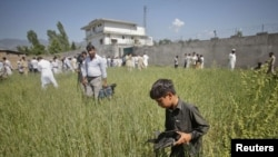 FILE: A boy collects debris as journalists surround the compound where al Qaeda leader Osama bin Laden was killed in Abbottabad (May 2011).
