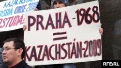"""Казахские беженцы проводят пикет в Праге. На плакате написано """"Прага-1968 = Казахстан-2009"""". 7 февраля 2009 года."""