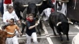 Spain -- Bulls run after the 'mozos' or runners during the first bullrun of the 2014 Sanfermines in Pamplona, 07 July 2014.